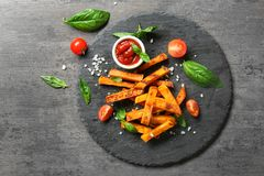Slate plate with sweet potato fries. On table Stock Image