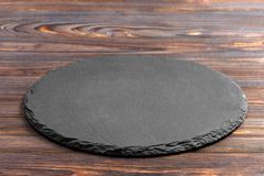 Slate plate on table. black slate stone on wooden background. copy space Stock Image