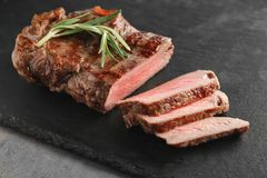 Slate plate with tasty grilled steak on grey background stock photo