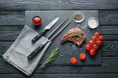 Slate plate with tasty grilled steak, sauce and fresh tomatoes on wooden table stock image
