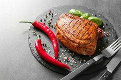 Slate plate with tasty grilled steak and spices on grey background stock photography