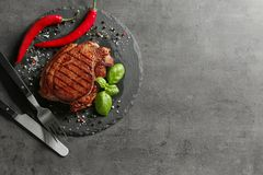 Slate plate with tasty grilled steak and spices on grey background royalty free stock images