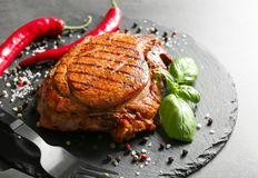 Slate plate with tasty grilled steak and spices on table stock images