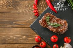Slate plate with tasty grilled steak and vegetables on table royalty free stock photo