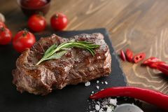 Slate plate with tasty grilled steak and vegetables on table royalty free stock images