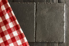 Slate plates and tablecloth. Empty slate plates and tablecloth over black wooden background Stock Image