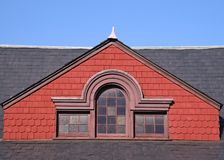 Slate Roof and Red Gable. Old building with a slate roof and an ornate red gable Stock Image