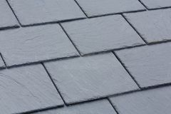 Slate roof tiles. Closeup of traditional grey slate roof tiles on a pitched roof stock images