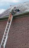 Slate Roof Worker. Roofing contractor on ladder repairing old slate roof Royalty Free Stock Photography