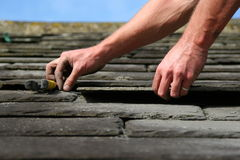 Slate roofing. Man replacing a slate on a roof Royalty Free Stock Photos