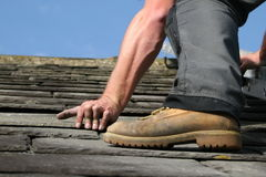 Slate roofing. Man replacing a slate on a roof Stock Photos