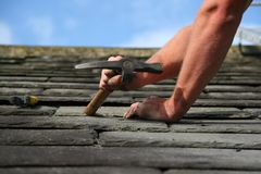Slate roofing. Man replacing a slate on a roof Royalty Free Stock Photo