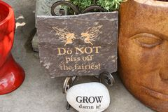 Slate sign saying Do Not of the fairies and a decorative rock that says GROW damn it beside two head planters on a patio stock photos
