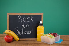 Slate with text back to school and breakfast on table. Against green background Royalty Free Stock Photography