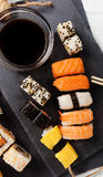 Slate tray of assorted sushi. Black slate tray of assorted sushi and rolls Stock Images