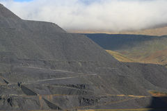 Slate waste. Waste products of slate quarrying in levels on a mountainside with zigzag paths and fences Stock Photo