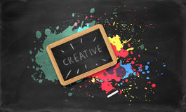 Slate in wooden frame, piece of chalk on black. Slate in wooden frame with the word creative on it and a piece of chalk on black background with colorful Stock Photo