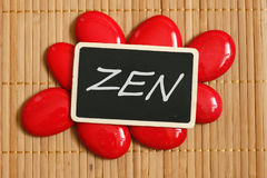 A slate with a zen message surrounded by red pebble and bamboo floor. Slate with a zen message surrounded by red pebble and bamboo floor stock photography