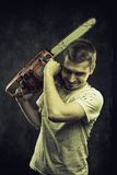Slaughter. Mad maniac with bloody chainsaw over grunge background royalty free stock photography