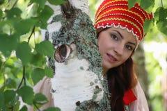 Slave dans la robe traditionnelle se cachant derrière des arbres Photos libres de droits