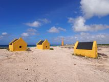 Slave huts on Bonaire. Historic yellow slave huts against cloudy blue Caribbean sky. A reminder of Bonaire colonial past, Dutch Antilles Stock Image