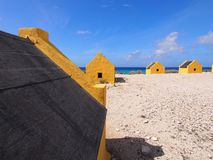 Slave huts on Bonaire. Historic yellow slave huts against cloudy blue Caribbean sky. A reminder of Bonaire colonial past, Dutch Antilles Stock Photos