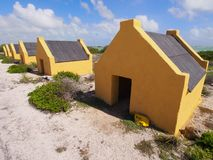 Slave huts on Bonaire. Historic yellow slave huts against cloudy blue Caribbean sky. A reminder of Bonaire colonial past, Dutch Antilles Royalty Free Stock Photography