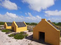 Slave huts on Bonaire. Historic yellow slave huts against cloudy blue Caribbean sky. A reminder of Bonaire colonial past, Dutch Antilles Royalty Free Stock Images