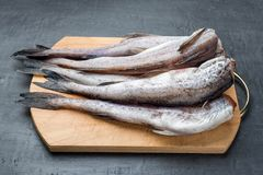 Slave raw Fish on wooden cutting Board on dark background.  Stock Photo