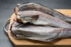 Slave raw Fish on wooden cutting Board on dark background.  Royalty Free Stock Photos