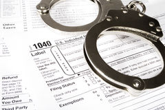 Slave to the taxes. Stock image of handcuffs over Tax forms, concepts: Tax fraud or Slave to the Taxes Royalty Free Stock Images