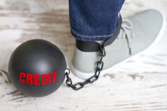 In slavery of credit concept with metal ball on chain and leg Stock Photography