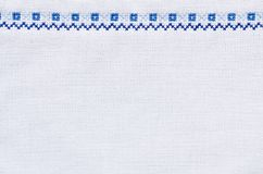 Embroidery texture for background. Slavic cross stitch by white and blue threads. Design of ethnic pattern. Embroidery texture for background Royalty Free Stock Photos