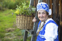 Slavic happy elderly woman in ethnic clothes outdoor in the village. Stock Photography
