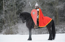 Slavic knight. On black horse Royalty Free Stock Photo