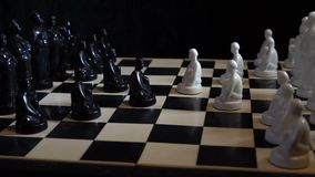 Slavische zwart-witte schaakstukken die zich op een schaakbord op een donkere achtergrond bevinden stock video
