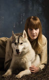 Slavonian girl and siberian husky in the deep forest Stock Photography