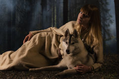 Slavonian girl and siberian husky in the deep forest Stock Images