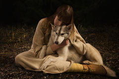 Slavonian girl and siberian husky in the deep forest Royalty Free Stock Photography