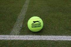 Slazenger Wimbledon Tennis Ball on grass tennis court. NEW YORK - JULY 2, 2019: Slazenger Wimbledon Tennis Ball on grass tennis court. Slazenger Wimbledon Tennis royalty free stock photos