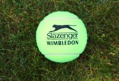 Slazenger Wimbledon Tennis Ball on grass tennis court. NEW YORK - JUNE 26 Slazenger Wimbledon Tennis Ball on grass tennis court on June, 26, 2014 in New York royalty free stock images