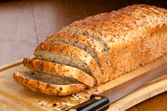 Slced loaf of bread. Sliced loaf of whole wheat bread with mixed seeds on breadboard Royalty Free Stock Photo