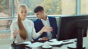 Slecht BedrijfsNieuws Twee jonge mensen die in het bureau werken stock videobeelden