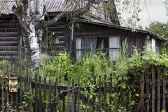 Slecht oud vernietigd huis in dorp Verlaten naar huis overwoekerde wi stock fotografie