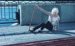 Slechte bejaarde dame die in openlucht vallen onderaan royalty-vrije stock foto