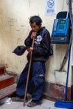 Slechte blinde lokale Indio-bedelaar die naast openbare telefoon voor aalmoes in de markt van Huaraz in Peru bedelen royalty-vrije stock foto's