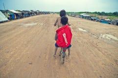 Slechte Cambodjaanse jonge geitjes die met oude fiets rennen Stock Foto