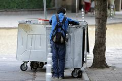 Slechte dakloze mens dichtbij vuilnisbakken stock fotografie