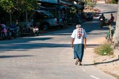 Slechte gebochelde oude mens die in exotische Aziatische straat lopen Stock Afbeelding