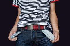 Slechte mens in jeans met lege die zak op zwarte wordt geïsoleerd stock foto's